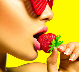 Fototapeta Owoce Sexy woman wearing glamour red sunglasses eating strawberry