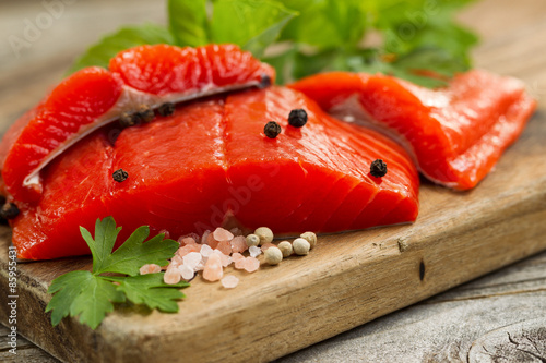 Canvastavla  Fresh Copper River Salmon fillets on rustic wooden server with s