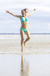 Woman happy and jumping high for life on beach