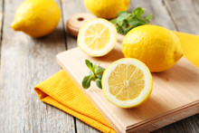 Lemons On Cutting Board On Grey Wooden Background