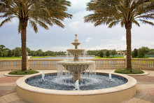 Fountain And Lake - Water Splashes From Tropical Fountain That Overlooks Lake Surrounded By Lush Greenery