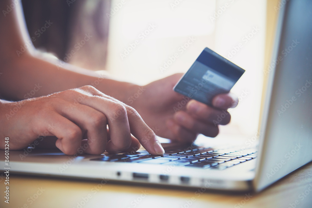 Fototapeta Hands holding credit card and using laptop. Online shopping