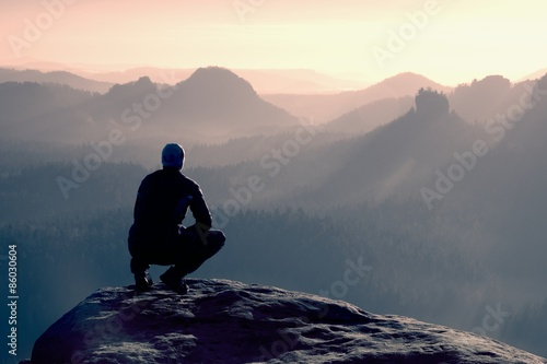 Canvastavla Young man in black sportswear is sitting on cliff's edge and looking to misty va