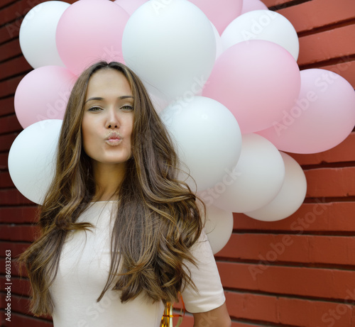 Photo Happy young woman standing over red brick wall and holding pink