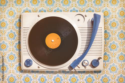 Fotografía  Vintage record player on top of flower wallpaper