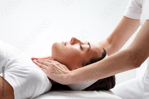 Therapist doing reiki on woman's neck. Canvas Print