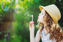 Little Girl Blowing Soap Bubbles In A Heart Shape. Happy Childho