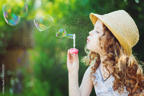 Fotografia Little girl blowing soap bubbles in a heart shape. Happy childho