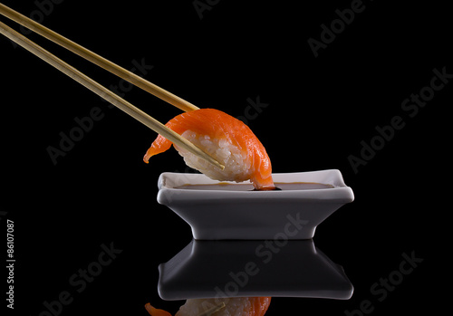 Poster Sushi bar Salmon sushi nigiri in chopsticks with soy sauce over black background