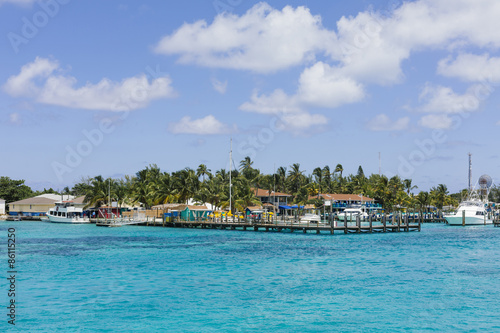 Foto op Canvas Tropical strand Image of a dock and a few sailing boats near some homes.