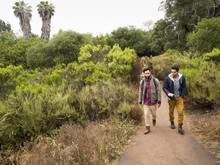 Two Young Men Walking In A Park.