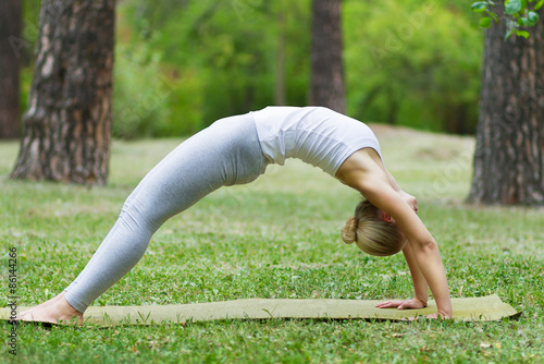 Foto op Aluminium Gymnastiek girl doing yoga and gymnastics on the grass
