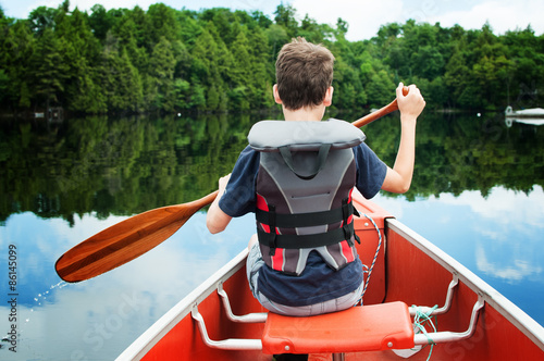 Fotografía child in the front of a canoe paddling on a calm Canadian lake