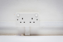 Universal Electric Socket Adapter On White Old Wall.