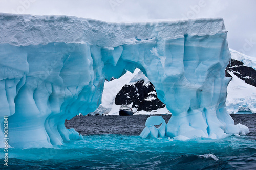 Poster Antarctica Huge blue iceberg with cruise ship in the distance, Antarctica