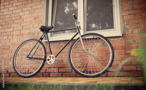 Fototapety, obrazy: Old style singlespeed bicycle against brick wall, tinted photo