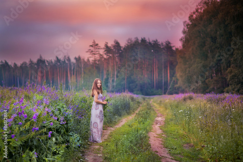 Poster Feeën en elfen Beautiful young woman standing in the meadow of violet flowers at sunset.