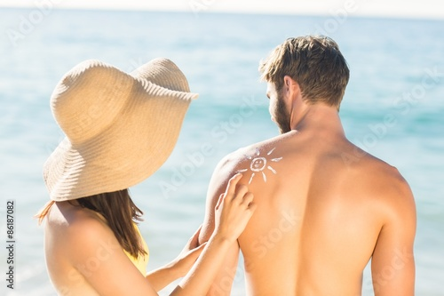 pretty brunette putting sun tan lotion on her boyfriend