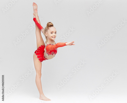 Foto op Aluminium Gymnastiek Teenage girl in red dress doing gymnastic exercises