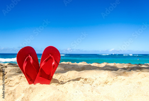 Red flip flops on the sandy beach