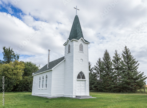 Papiers peints Edifice religieux horizontal image of a beautiful quaint little country church sitting on a green lawn surrounded by spruce trees under a white puffy cloud filled sky in the summer time.