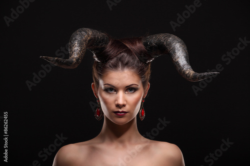 Foto  The beautiful young girl with horns like devil or angel