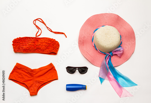 Fotografie, Obraz  Orange bikini swimsuit and accessories on white background.