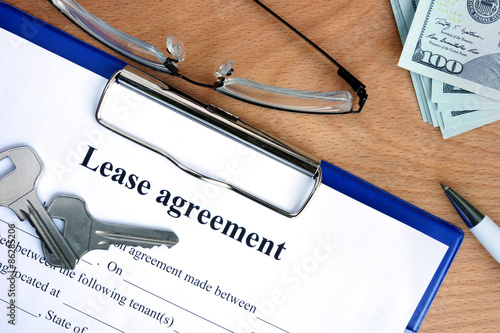Fotografía  Lease agreement document with money on a wood background