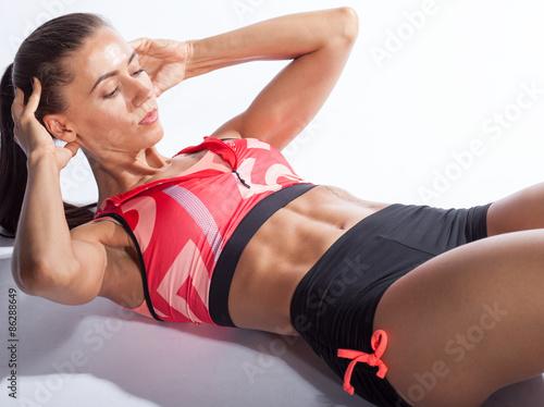 Fotografía  Hermosa mujer deportivo haciendo ejercicio para abdominales sobre fondo blanco