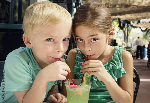 Valokuva  Cute kids sharing a mint julep drink at a cafe