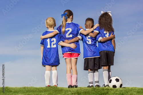 Fotografija  Diverse group of boys and girls soccer players standing together with a ball aga