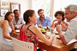canvas print picture - Friends sitting at a table talking during a dinner party