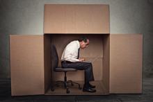 Man Sitting In A Box Working On Laptop Computer