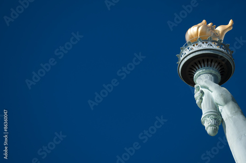 Tablou Canvas Statue of Liberty close-up torch against bright blue American sky