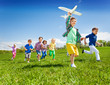 canvas print picture Active running kids with boy holding airplane toy