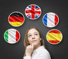 Beautiful Lady Is Surrounded By Bubbles With European Countries' Flags (Italian, German, Great Britain, French, Spanish). Learning Of Foreign Languages Concept. Blackboard Background.