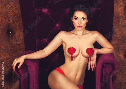 Sexy beautiful brunette woman posing sitting naked with stikini on nude breasts in a luxury velvet armchair, looking at camera