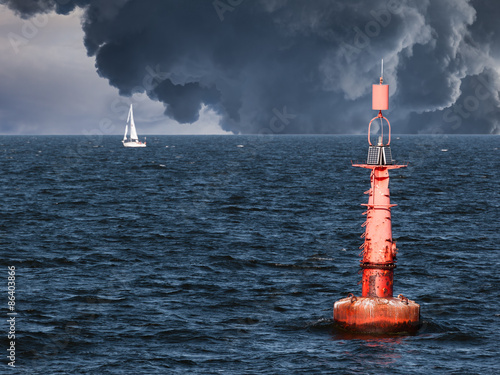Photo Red buoy on water in a stormy day.