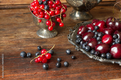 Poster Vruchten cherry with red currants and blueberries in a jug and a metal pl