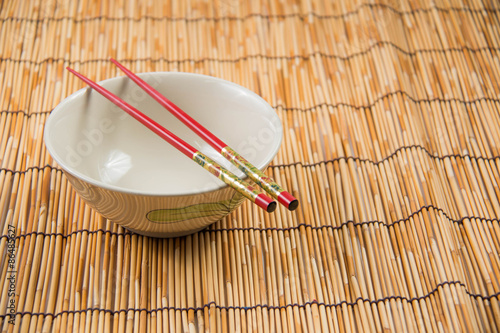Foto  bowl and chopsticks on bamboo mat.