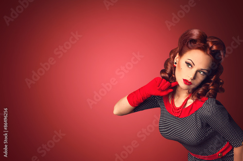 Photo  Red hair beautiful curious pin-up girl on a red background space board