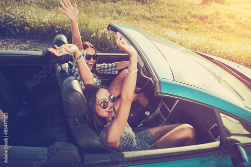 Two attractive young women in a convertible car Slika na platnu