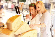Two Women Shopping For Cheese ...