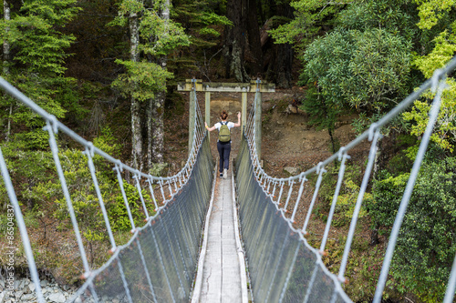 Staande foto Oceanië young adult woman passes the river on a suspension bridge on the