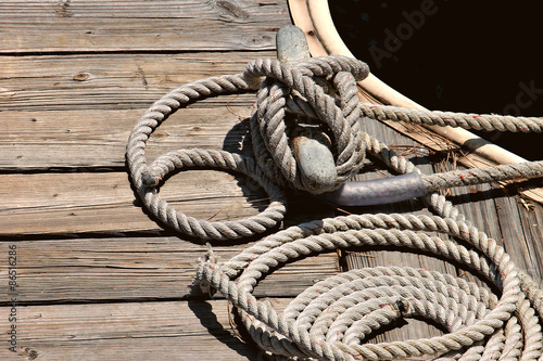 Fotografia  Deatil of boat tied to a woodn dock with nautical rope