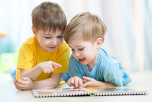 Kids Brothers Practice Reading Together Looking At Book Laying On The Floor