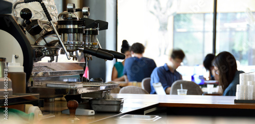 An espresso machine in a busy coffee shop with unrecognizable people in the background