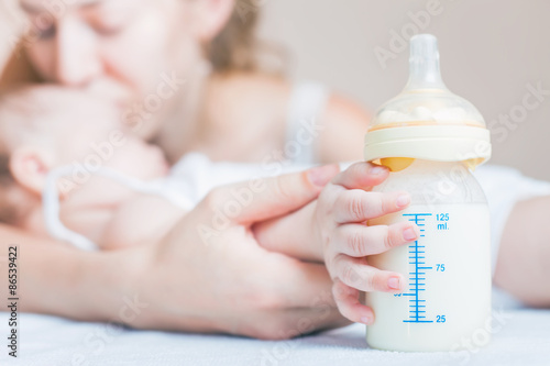 Obraz Baby holding a baby bottle with breast milk for breastfeeding. Mothers breast milk is the most healthy food for newborn baby. - fototapety do salonu