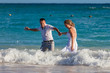 Young wedding couple have a fun in ocean waves