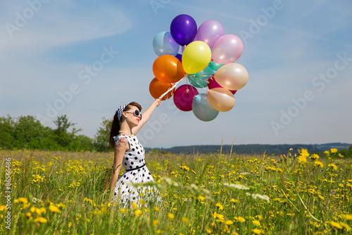 Valokuva  Junge Frau im Retro Look und vielen bunten Luftballons auf einer